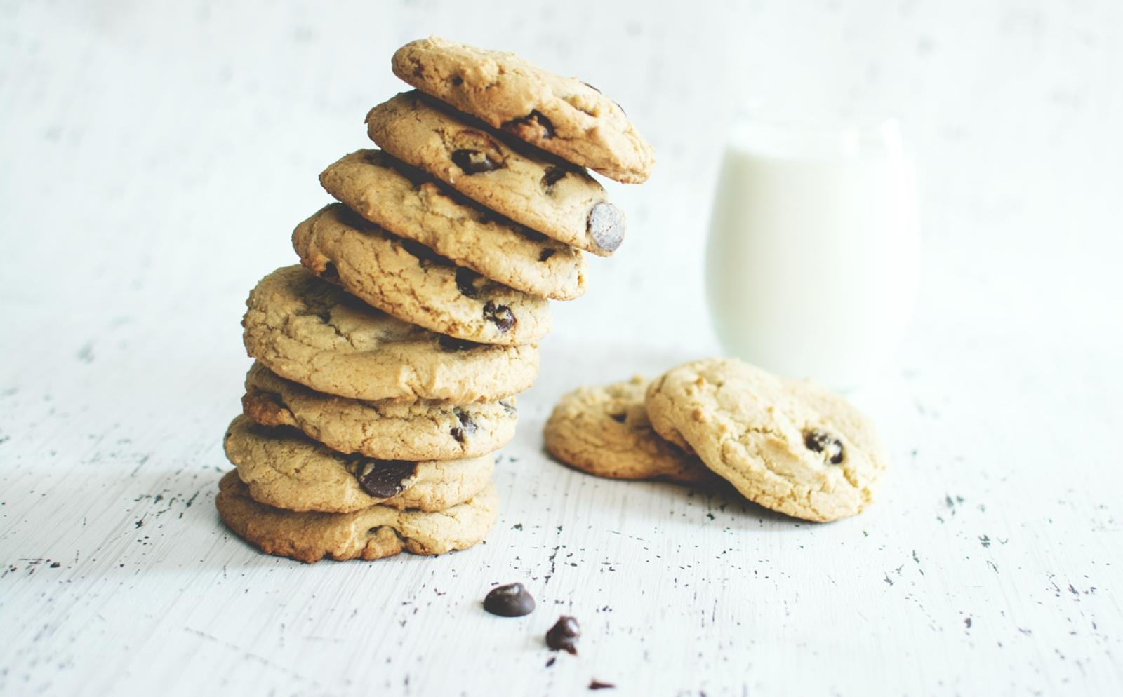 積み上げられたチョコチップクッキーとコップ一杯の牛乳